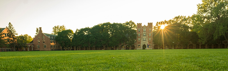 Gates Tower on the campus of Grinnell College. The sun is peaking through the trees which flank the Eastern Side of the tower (Mac Field Side).