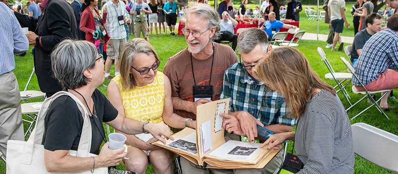A group of alumni reminisce while looking at an old picture album.