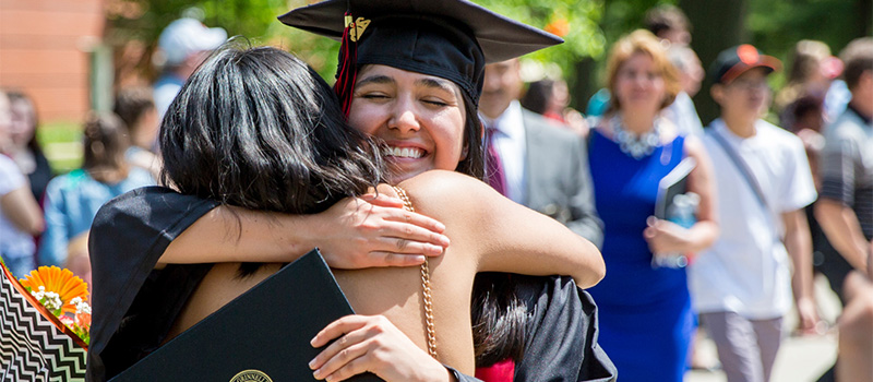 A student wearing a commencement cap and gown hugs a family member.