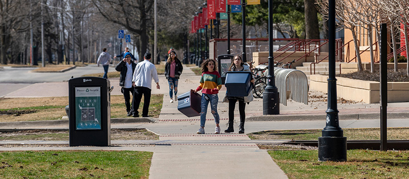 Grinnell students carry totes through campus to pack their belongings before heading back home.