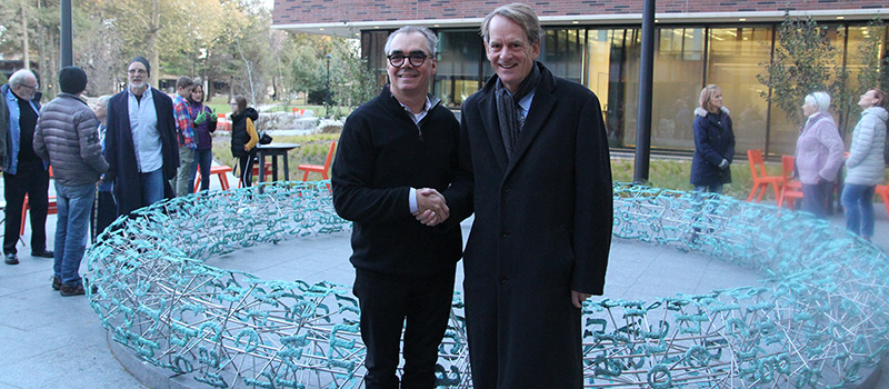 Former Grinnell College swimming teammates, Gregory Gómez '80, left, and John Chambers '77 share a handshake in front of the new sculpture.