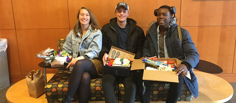 Students display the care packages they chose from the distribution table.