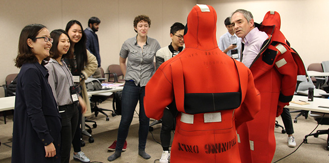 Mark Zimmermann '86, right, a research fishery biologist, puts on a wetsuit for students during their tour of the Alaska Fisheries Science Center in Seattle.