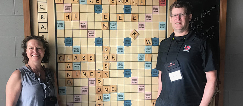 Co-class agents Irene Faass '91, left, and David Gassaway '91 stand in front of an oversized Scrabble board at Hotel Grinnell.