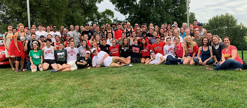 A reclining Evelyn and Will Freeman, front left, are joined by student-athletes, alumni, and friends at the finish line of the Les Duke Invitational.