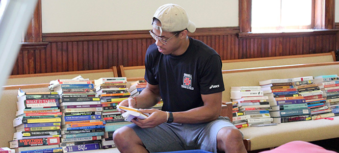 Erik Henderson '19 sorts and packs books for the New Student Orientation flea market during the 2017 Global Day of Service.