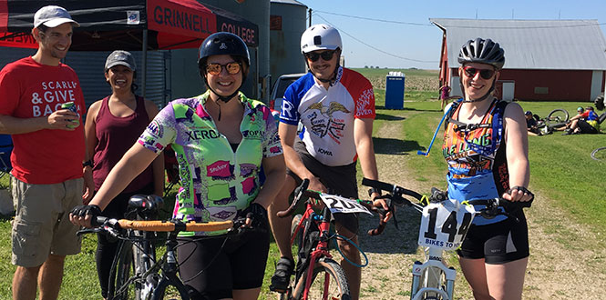 Dan Covino '10, far left, and Vrinda Varia were among the volunteers helping with the Grinnell group project during the Prairie Burn 100 bicycle ride.