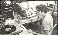 A DJ plays a record at the KDIC studio during the 1977-1978 school year