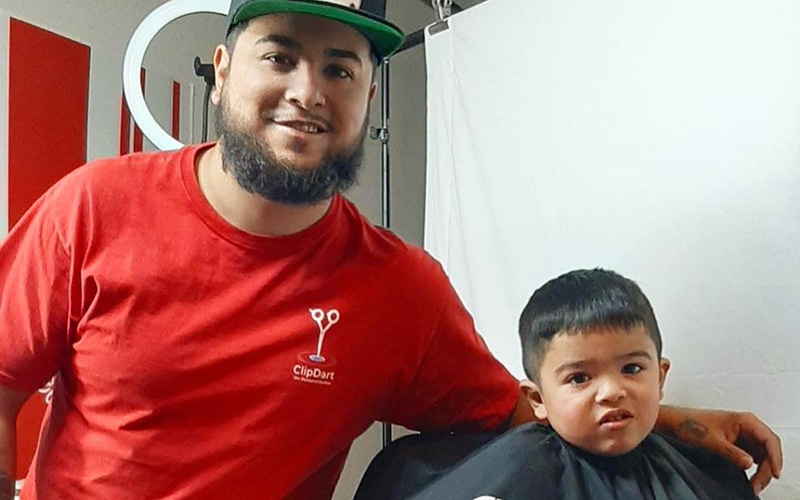 A barber and a young boy pose for a photo during an event ClipDart organized in Phoenix.