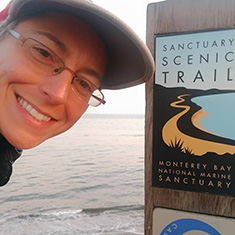 Natalie Larson '06 - selfie with a sign for the Sanctuary Scenic Trail
