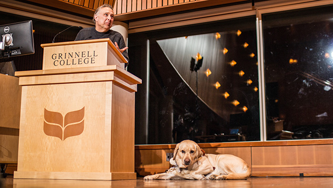 Author Stephen Kuusisto reads from his book while Caitlyn, a yellow Labrador guide dog, looks on.