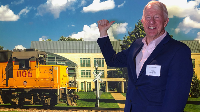 Mike Daley stands in front of a Grinnell photo background at the College's 2019 campaign event in Chicago.
