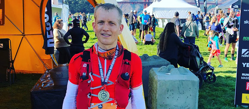 Neil Martin '99 poses after getting his completion metal after the 2017 50 mile Endurance Challenge in San Francisco.