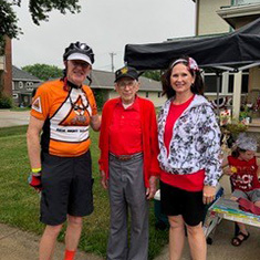 Mike Daley '72, left, 104 years young George Wertz, and Tuesday, pose for a group photo outside a home in Walnut on the first day of RAGBRAI.