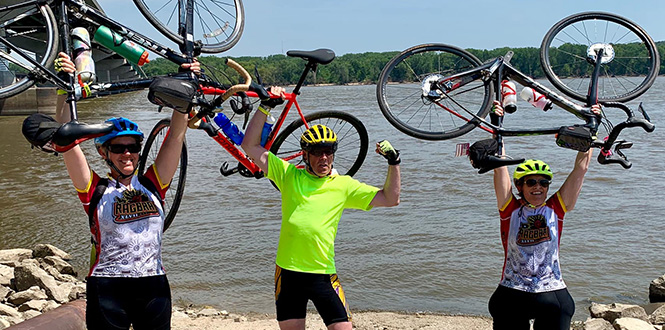 Betsy Mathre Quist '86, left, Dan McGrath '86, and Sarah Jolie '87 celebration the completion of RAGBRAI in front of the Mississippi River.