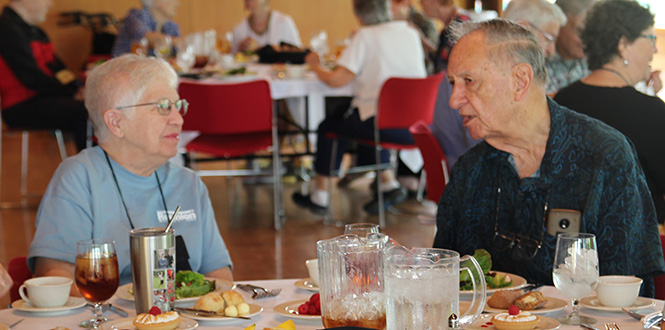 Arthur Dercksen '54, right, shares a story with Jan Ashley Bowen '59 during the Golden Luncheon Friday at the Joe Rosenfield '25 Center.