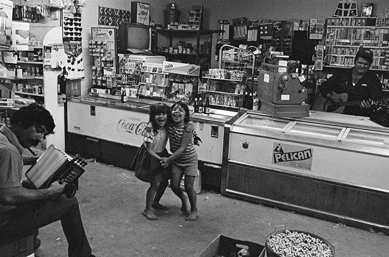 Two girls dance as musicians play in a Louisiana store during the 1970s. The photograph appears in Ron Stanford's book, Big French Dance: Cajun & Zydeco Music, 1972-74.