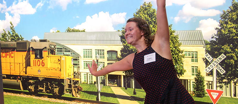 Neems playfully attempts to stop the Union Pacific train in front of a campus photo backdrop at the Washington D.C. campaign event.
