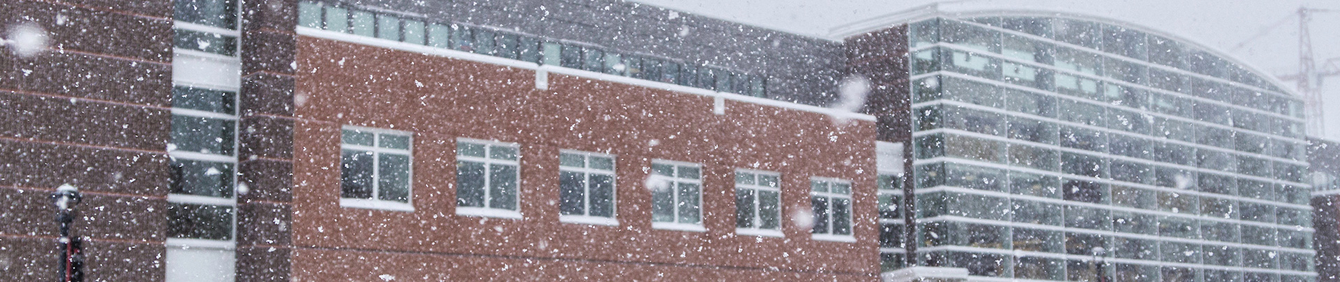 Snow falls in this picture of the front of Noyce Science Center.