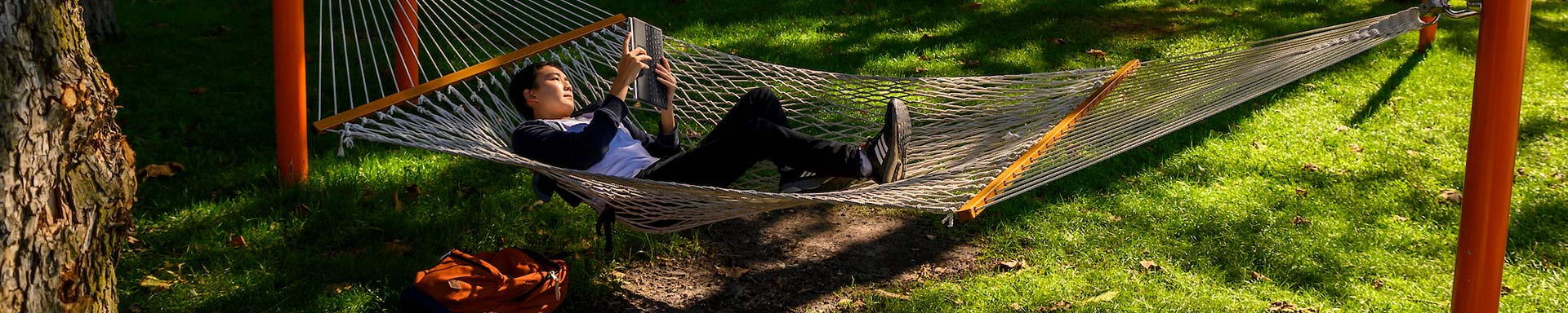 A student reads a book while laying in a hammock on campus.