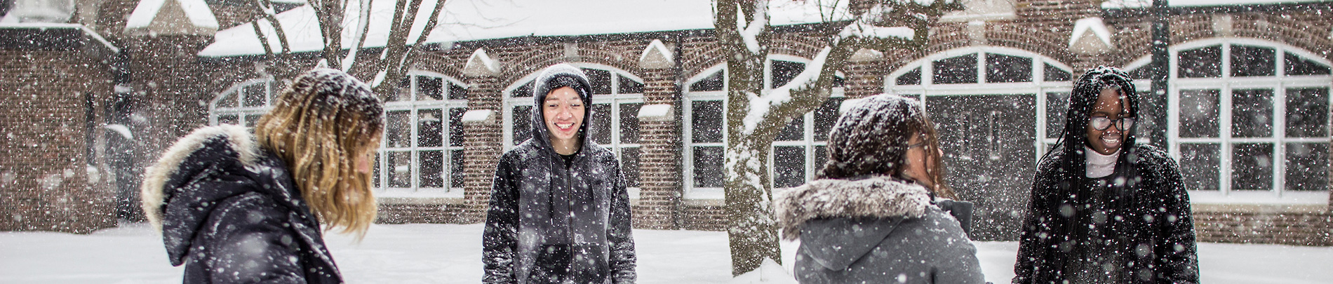 International students play in the snow.