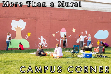 Text: Campus Corner - More than a Mural. Image: Mural being painted in Grinnell on a brick wall. The images in the mural include a tree, a child on a bike, the Grinnell Watertower, and other images.