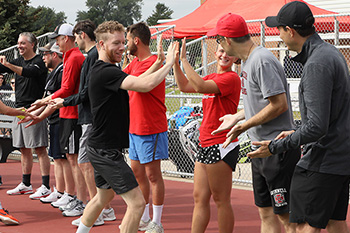 The tennis team runs through a high five line.
