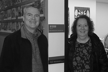 Kevin Rhodes '85 and Melinda (Lindy) Lopes '85 stand in front of the Lopes Rhodes Dirty Teaching Lab in the HSSC.