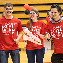 Three students hold a sign that says Thank You on Scarlet and Give Back Day.