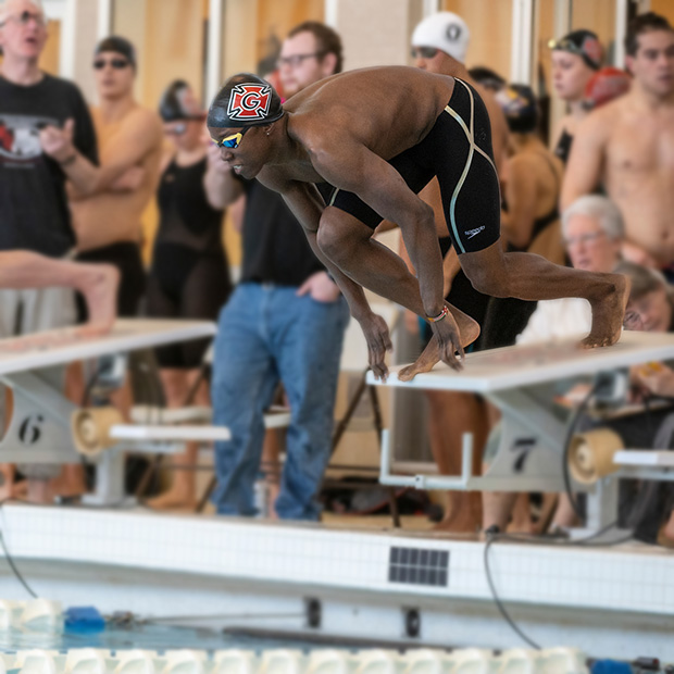 A Pioneer swimmer launches of the block to start a race.