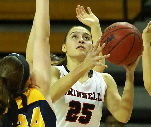 Grinnell Women's Basektball Player jumps for a shot among a sea of arms.