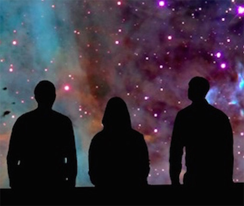 People silhouetted against a galaxy map.
