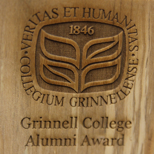 Picture of the Alumni Award Plaque featuring the Grinnell College Seal burned into wood harvested from trees on campus.