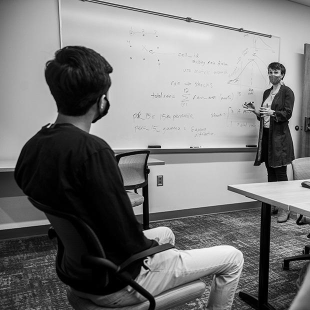 Tamara McGavock, economics assistant professor teaches from a whiteboard.