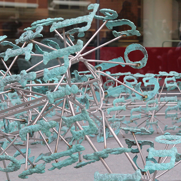 Close up image of the sculpture Broken English on the campus of Grinnell College.