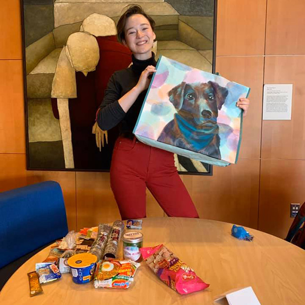 A student displays the contents of the Care Package she received which includes a painted canvas bag featuring a black lab.
