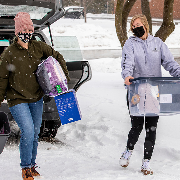 Two students carry boxes and possessions while moving into the dorms with snow on the ground.