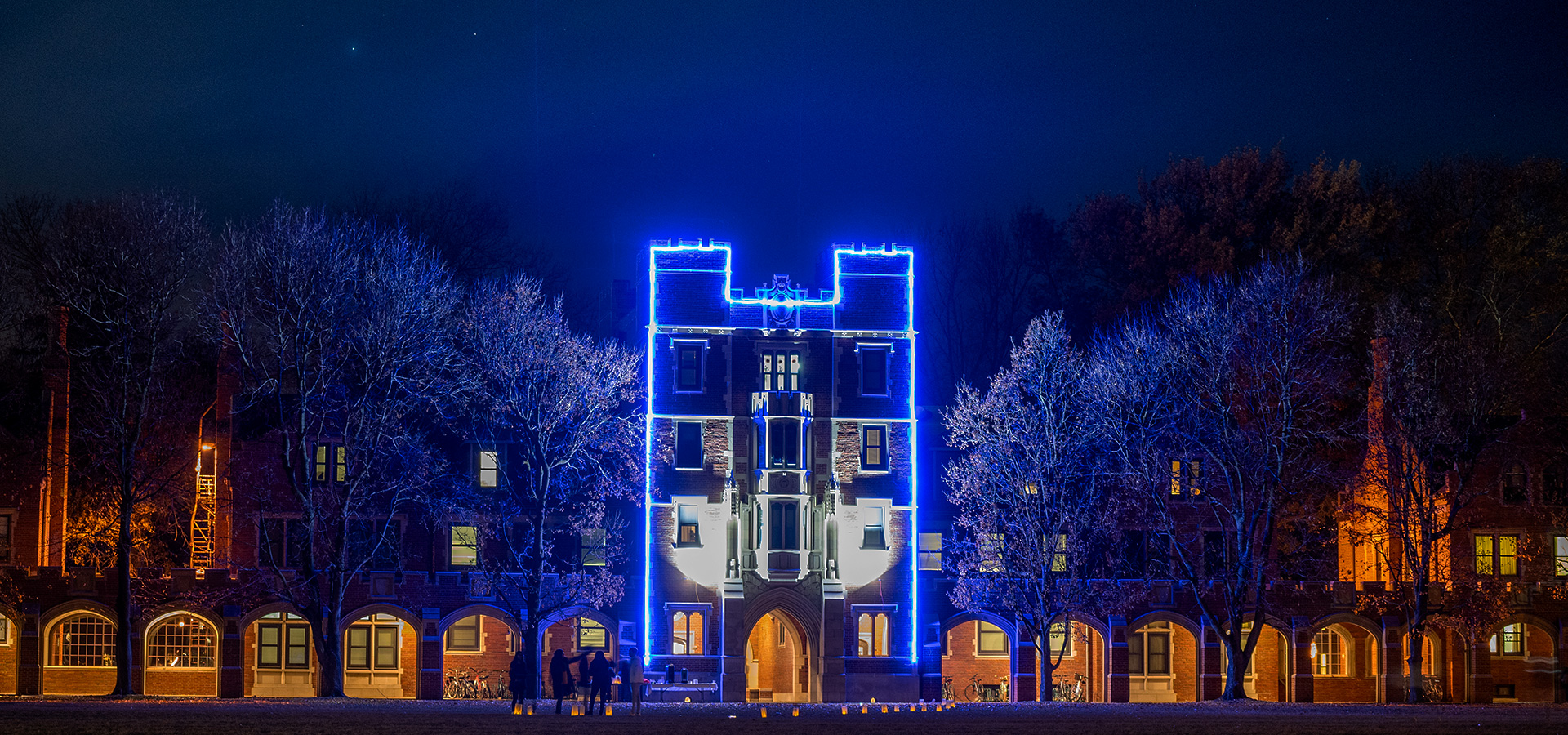 Gates Tower on the campus of Grinnell College. The outline of the tower is lined with Christmas Lights which allows the shape of the building to cut through a light haze.